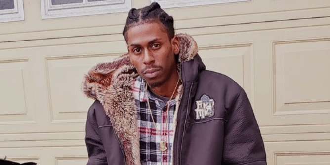 Photo of Jamal Francine in an open coat in front of a garage